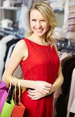 Portrait of smiling woman with paperbags looking at camera after shopping in clothing department