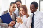 Group of modern managers looking at cellphone in hands of female employee