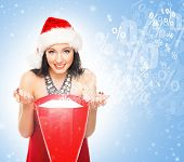Woman in Christmas hat over snowy background.  Winter shopping concept.