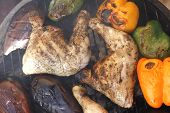 fresh group of grilled chicken thighs with green orange yellow pepper bell slice and eggplants on hot grill bbq