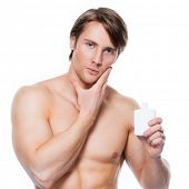 Young handsome man applying lotion on face - isolated on white.