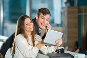 Flirting couple in cafe using digital tablet and telephone, selective focus