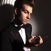Handsome young elegant man looking down while enjoying a cigarette.