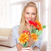 Portrait of beautiful happy woman with autumn flowers at home, receive gift on Thanksgiving day, happiness concept