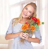 Portrait of cheerful smiling female with flowers bouquet in hands, spending autumn holiday at home, enjoying cute present