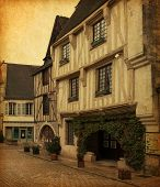 Old houses on  Place de l'hotel de ville,   Noyers-sur-Serein, Yonne, Burgundy, FRANCE.  Photo in retro style. Paper texture.
