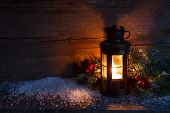 Christmas lantern, fir twigs and artificial snow in night on old wooden background.