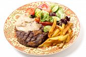 Dinner plate of grilled rib-eye beef steak served with mushroom sauce, salad and potato chips.