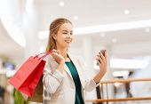 sale, consumerism, technology and people concept - happy young woman with smartphone and shopping bags taking selfie in mall