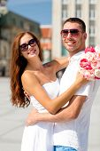 love, wedding, summer, dating and people concept - smiling couple wearing sunglasses with bunch of flowers hugging in city