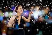people, shopping, sale, christmas and holidays concept - smiling woman in dress with shopping bags over night lights and snow background