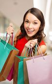 happiness, consumerism, sale and people concept - smiling young woman with shopping bags over mall background