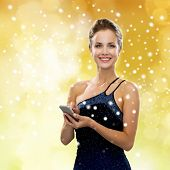 technology, christmas, holidays and people concept - smiling woman in evening dress holding smartphone over yellow lights and snow background
