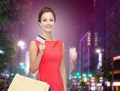 people, sale, christmas and holidays concept - smiling elegant woman in red dress with shopping bags and credit card over night city background