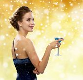 party, drinks, holidays, people and christmas concept - smiling woman in evening dress holding cocktail over yellow lights and snow background