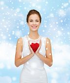 happiness, health, charity and love concept - smiling woman in white dress with red heart over blue cloudy sky and snow background