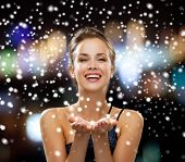 people, holidays, advertisement and christmas concept - laughing woman in evening dress holding something imaginary over night lights and snow background