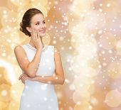 engagement, celebration, wedding and happiness concept - smiling woman in white dress wearing diamond ring over beige lights background and snow