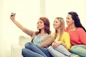 friendship, technology and internet concept - three smiling teenage girls taking selfie with smartphone camera at home