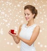wedding, love, engagement and happiness concept - smiling woman in white dress holding red gift box with diamond ring over beige background and snow