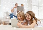 family, home, technology and people - smiling mother, father and little girls with tablet pc computer over snowflakes background