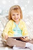 childhood, toys, technology and happiness concept - smiling little girl with tablet pc computer sitting on sofa at home