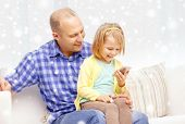 family, childhood, parenthood, technology and people concept - happy father and daughter with smartphone at home