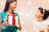 christmas, holidays, family and people concept - happy mother and child girl with gift box over beige background