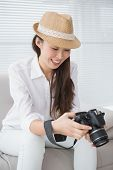 Photo editor looking at her camera in creative office