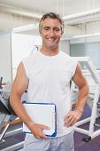 Fit personal trainer smiling at camera in fitness studio at the gym