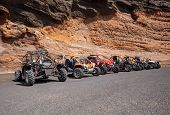 Buggies in front of a wall of rock