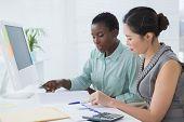 Businesswomen working together at desk in creative office