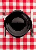 knife and fork at plate on napkin background