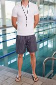Low section of a swimming coach standing by the pool at leisure center