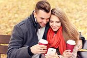 A picture of a young couple on a bench with smartphone in the park