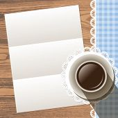Paper with cup with lace doily and ribbon border on wood