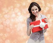 Pretty woman hands a present wrapped in red paper with white bow on gold light background