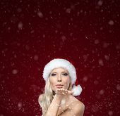 Beautiful woman in Christmas cap blows kiss, purple background