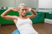 Beautiful young woman doing abdominal crunches on fitness ball in gym