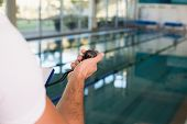 Close up of a cropped swimming coach with stopwatch by the pool at leisure center
