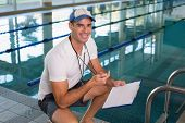 Portrait of a swimming coach with stopwatch by the pool at the leisure center