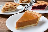 Closeup of four slices of pie on dessert plates. Focus is on the front slice of pumpkin pie. The back plates have apple and cherry pie. Horizontal format on an old wood kitchen table.