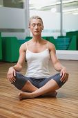 Full length of a sporty young woman sitting with eyes closed in fitness studio