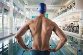 Rear view of a shirtless fit swimmer by the pool at leisure center