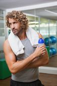 Handsome young man holding water bottle at the gym