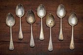 a row of vintage silver spoons with patina and scratches against grunge wood background