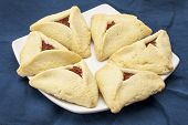 apricot hamantaschen cookies  on a plate against blue tablecloth - a traditional pastry in Ashkenazi Jewish cuisine for holiday of Purim