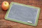 blank slate blackboard with chalk and apple against grunge red barn wood