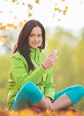 Young happy brunette woman listening to music in autumn park.