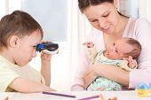 Boy Looking Through Binoculars At The Newborn